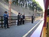 発車するトロッコ列車を見送る駅員以下多数